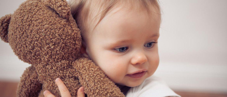 baby girl cuddling with a teddy bear