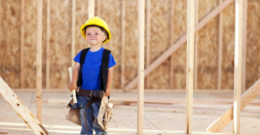 A happy little boy wants to be a carpenter when he grows up. He'll hammer it out for you.